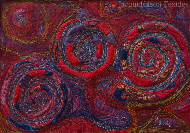 """Blue Spirals"" textile piece: embroidered red, purple and blue spirals on a red, gold and purple background."