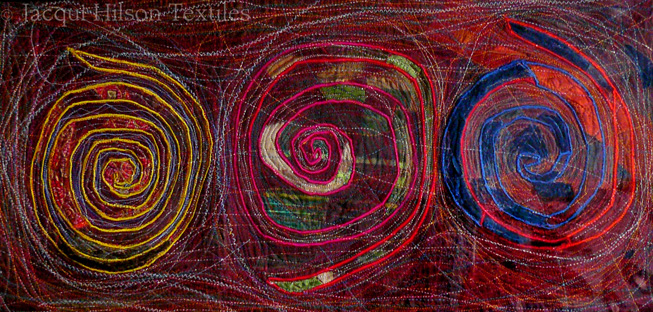 """Spirals"" textile: three spirals in yellow, red/green and blue/orange on a red and white embroidered background."