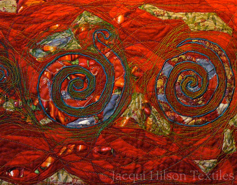 """Vintage Spirals"" textile piece: three green spirals with cutout panels of vintage cloth shown beneath, on an embroidered red background.."